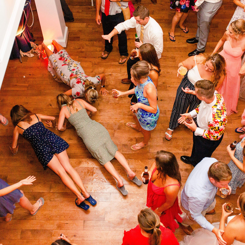 wedding guests watch 3 women do pushups on dance floor
