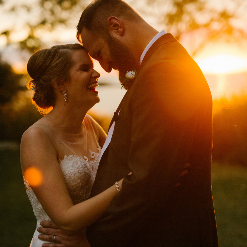 bride and groom laugh with heads together during sunset