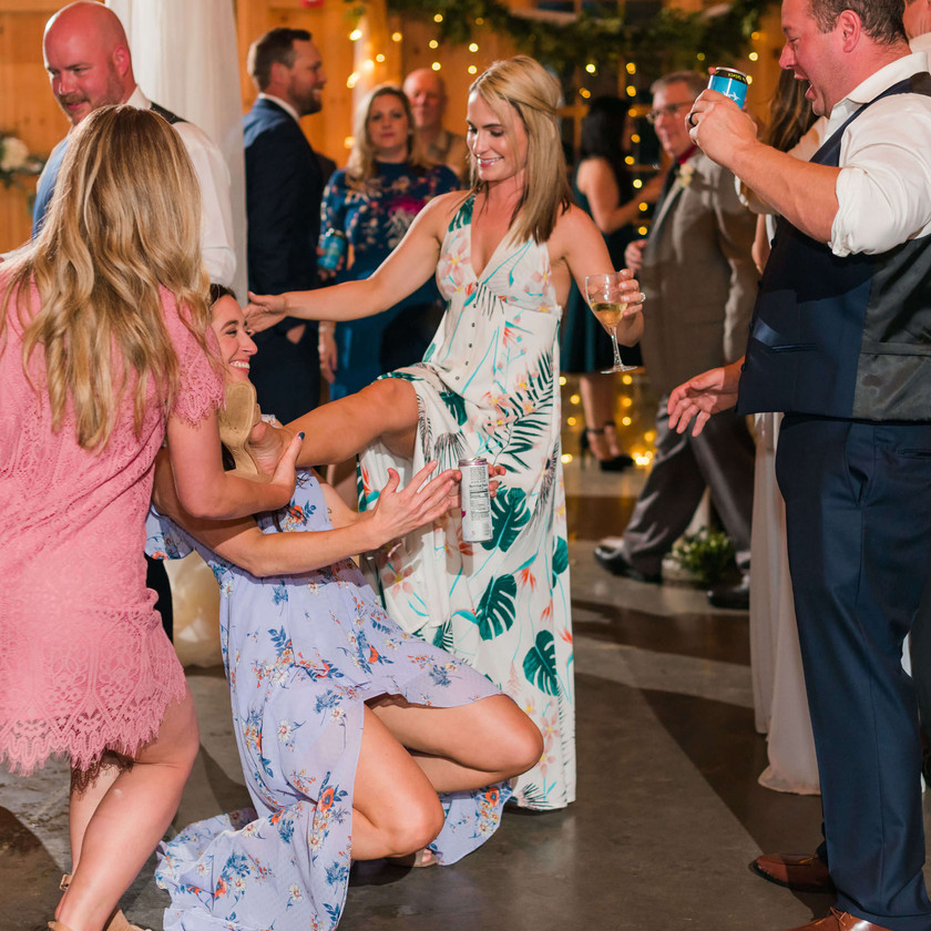 woman using leg as limbo stick with other woman going under