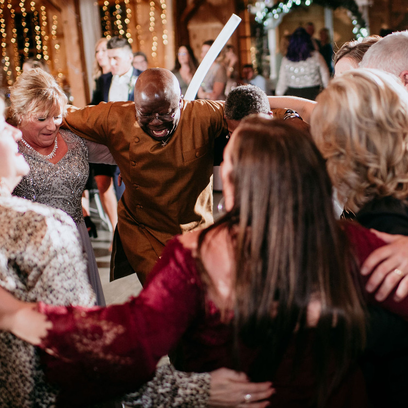 wedding guests dance while in a circle arm in arm