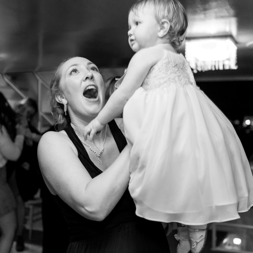 woman holding up little girl while dancing