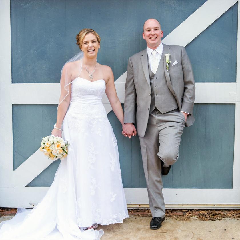bride and groom posing in front of blue door