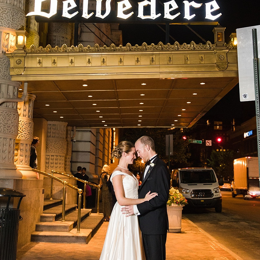 bride and groom pose in front of hotel sign