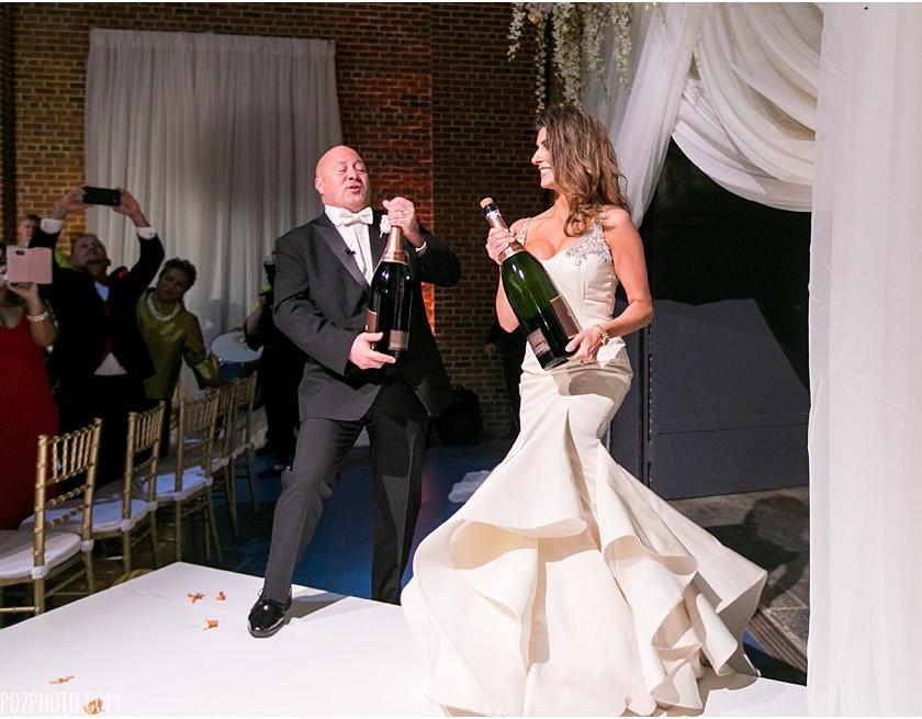 bride and groom shake large champagne bottles