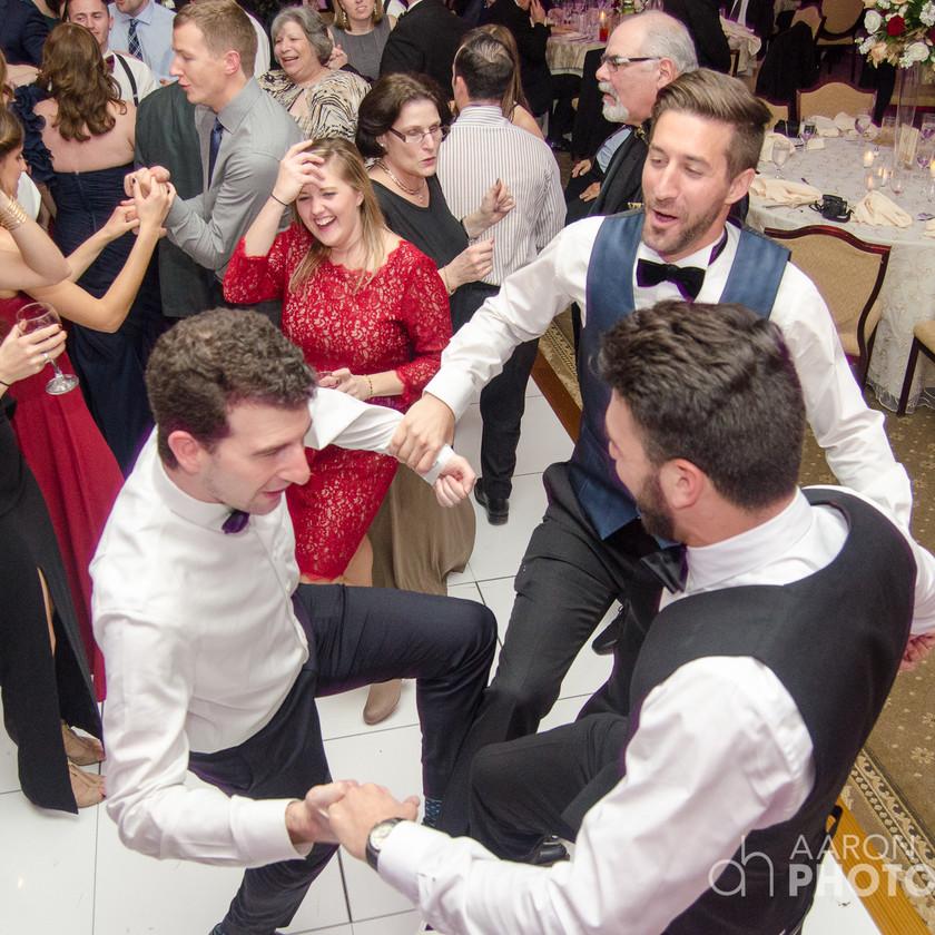 three guys dance together at wedding