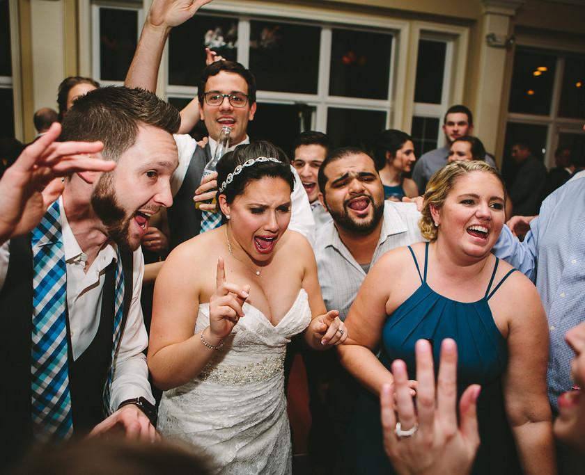 bride, groom, and wedding guests sing on dance floor
