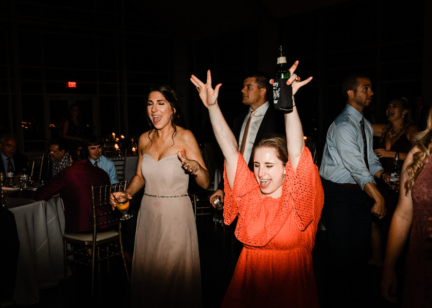 woman in orange dress dancing with hands up at wedding