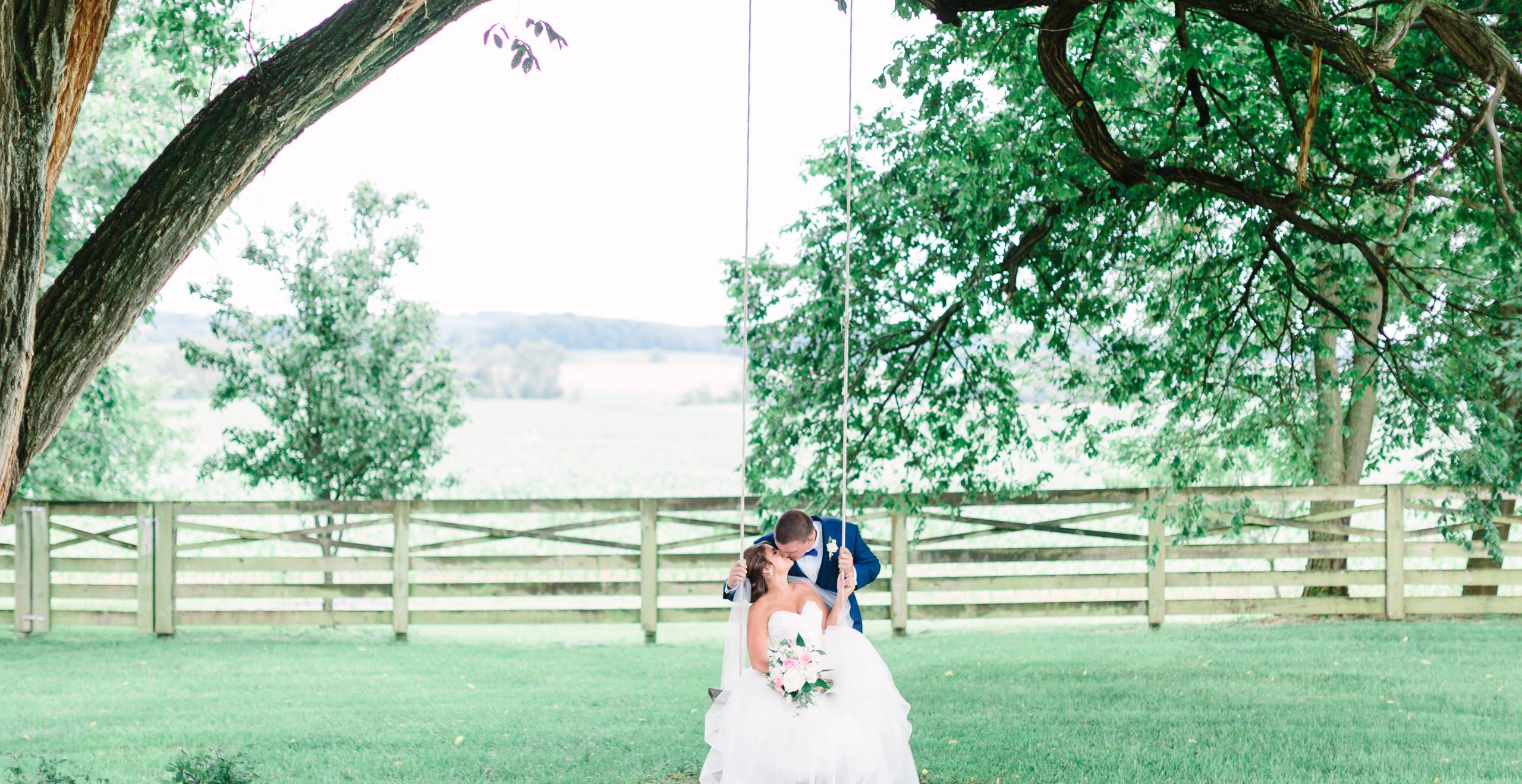 groom kissing bride sitting in swing