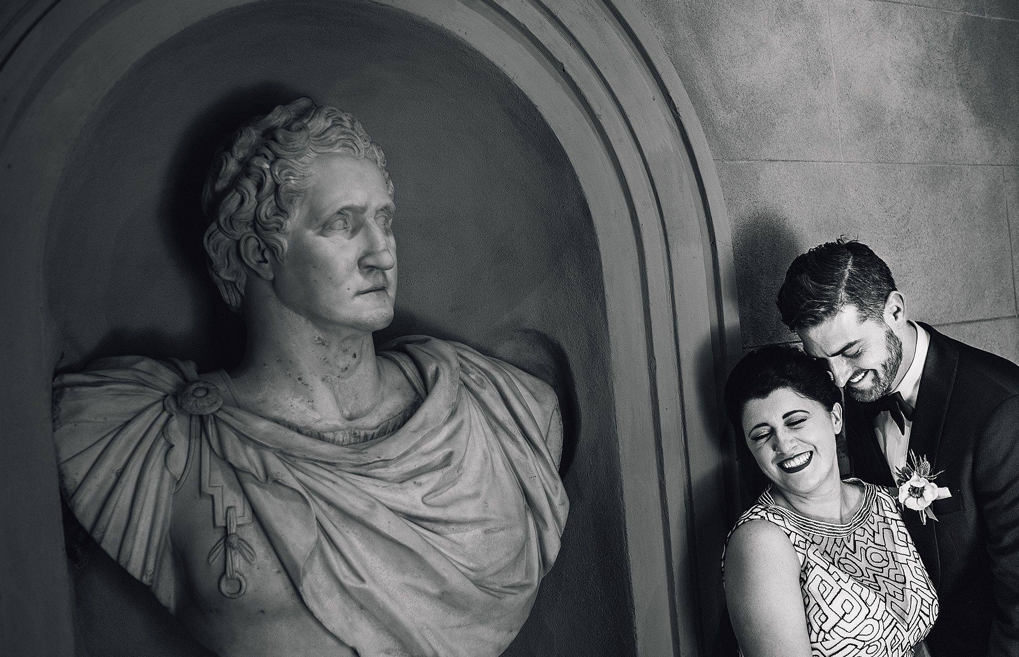 bride and groom laugh next to roman bust