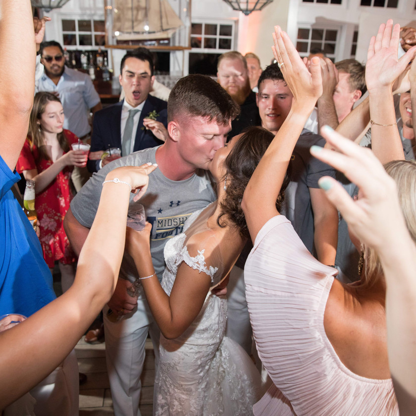 bride and groom kiss surrounded by friends on dance floor