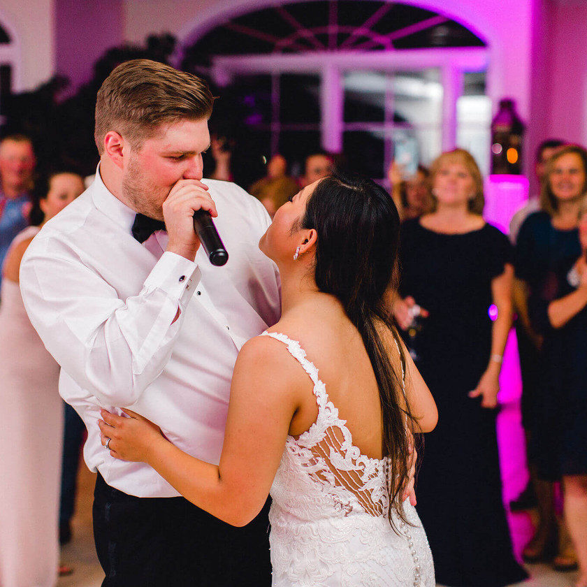 groom sings into mic while dancing with bride