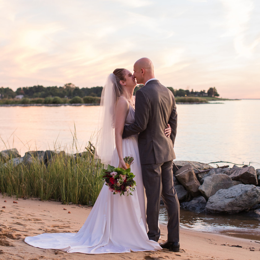 bride and groom kiss on small beach during sunset