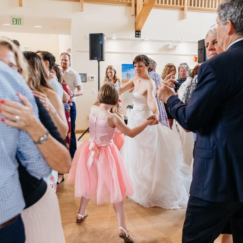 bride dancing with girl in pink dress
