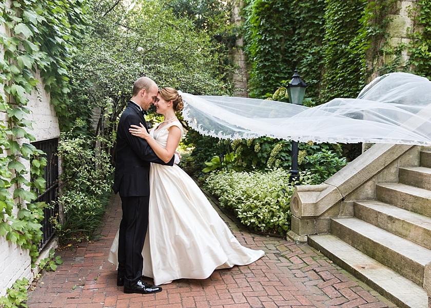 bride and groom pose in garden walkway with veil flowing