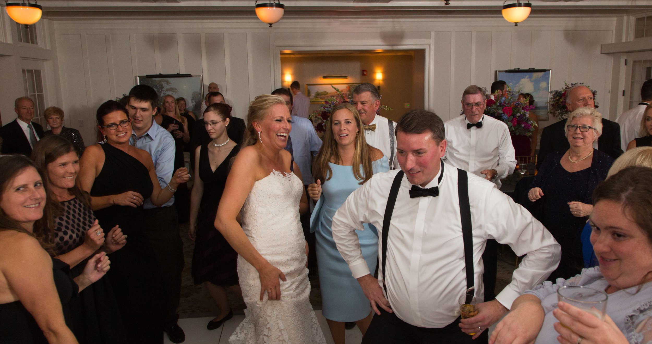 groom dances with hands on hips with bride and guests watching