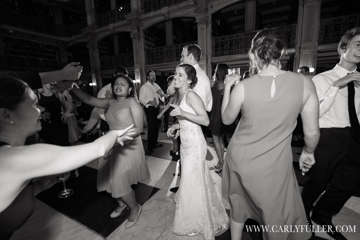 bride smiling and dancing at wedding surrounded by friends