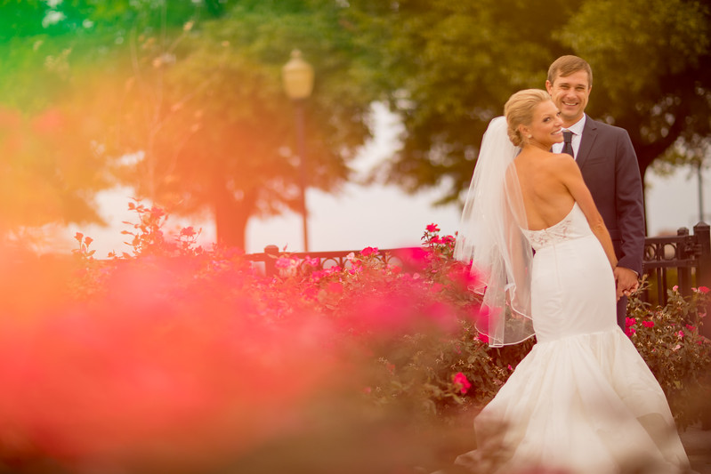 bride and groom smile by the roses
