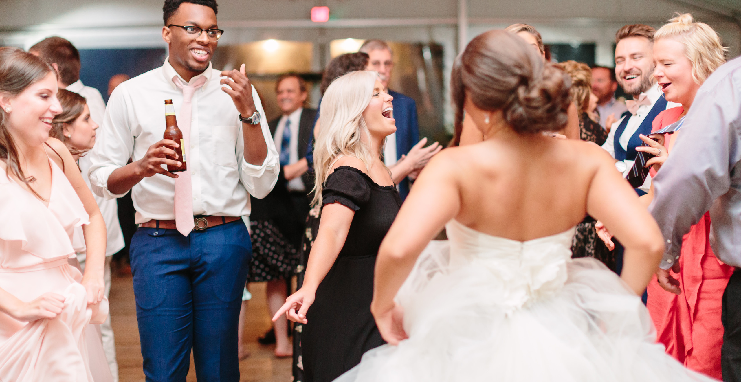 guests smiling and dancing with bride