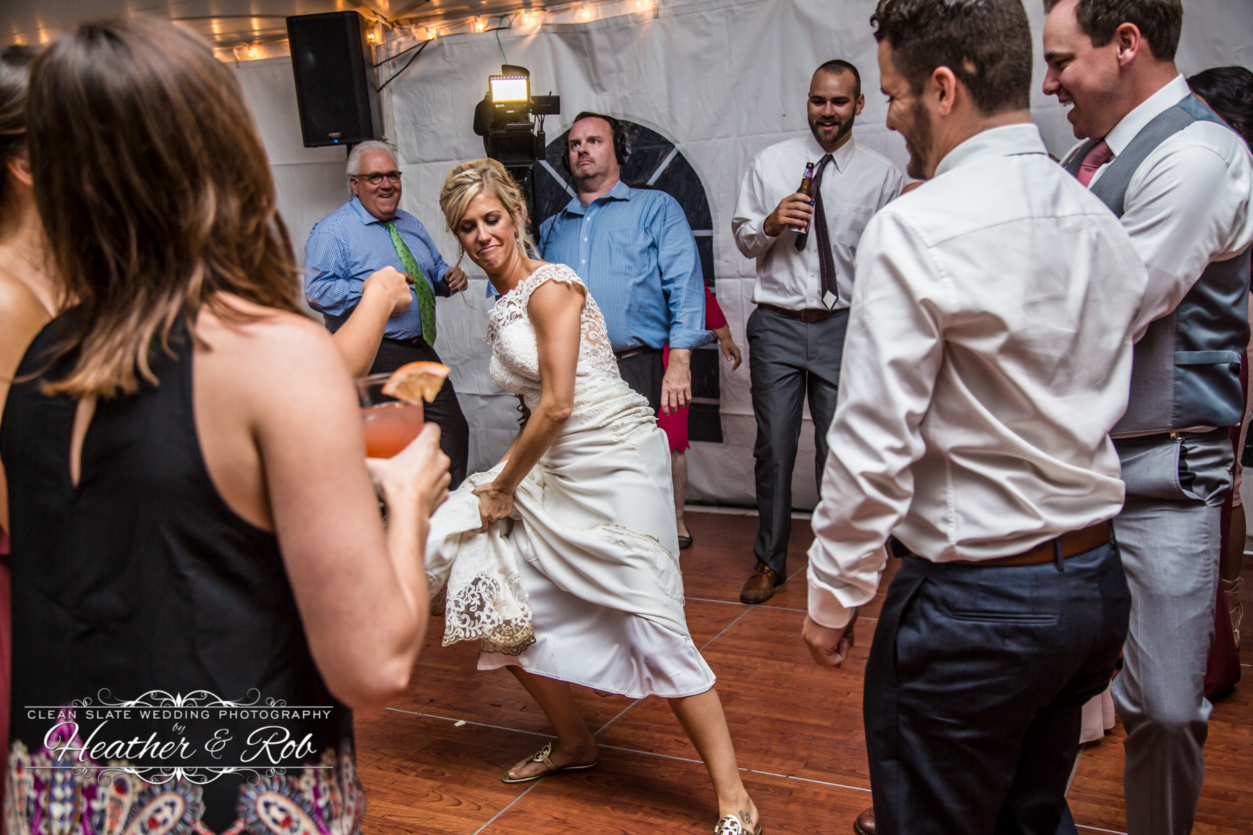 bride lifting up dress to dance at wedding