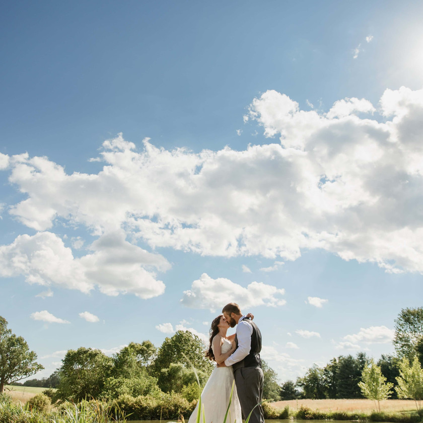bride and groom kiss under a beautiful blue sky