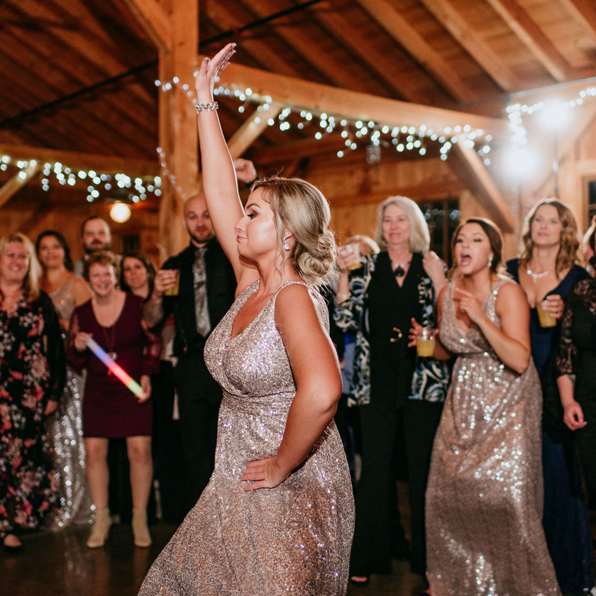 bridesmaid dances while surrounded by guests on dance floor