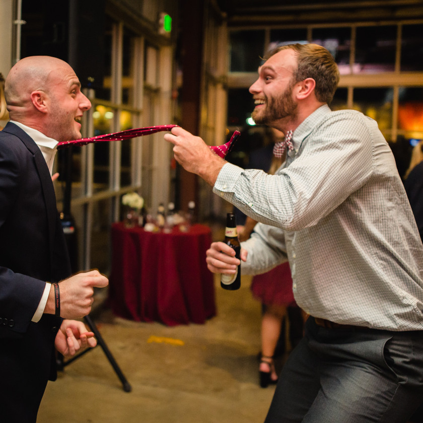 one guy pulls other guy by the tie dancing at wedding