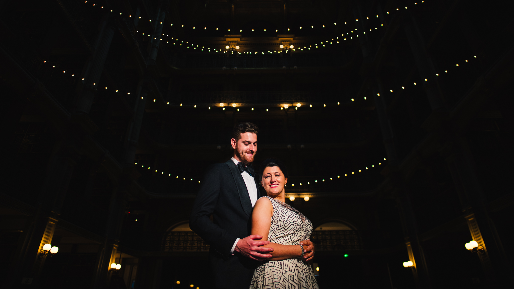 bride and groom stand underneath string cafe lights