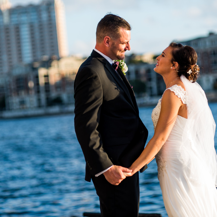 bride and groom look at each other by the baltimore harbor