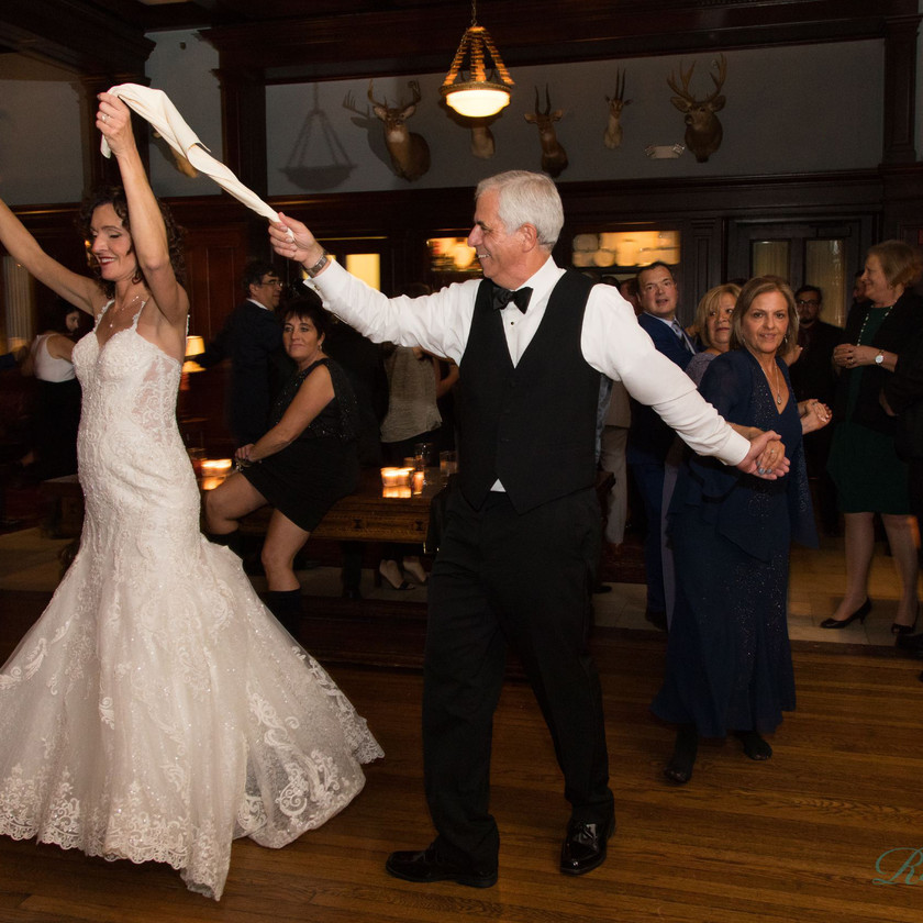bride and groom dance in line connected by napkin