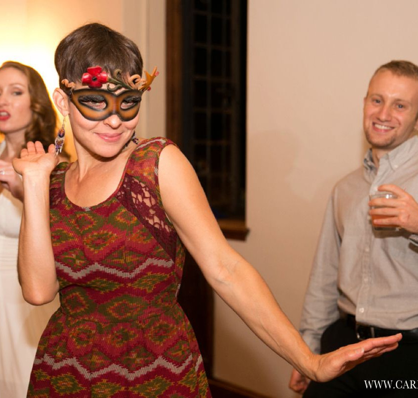 woman in mask dances at wedding