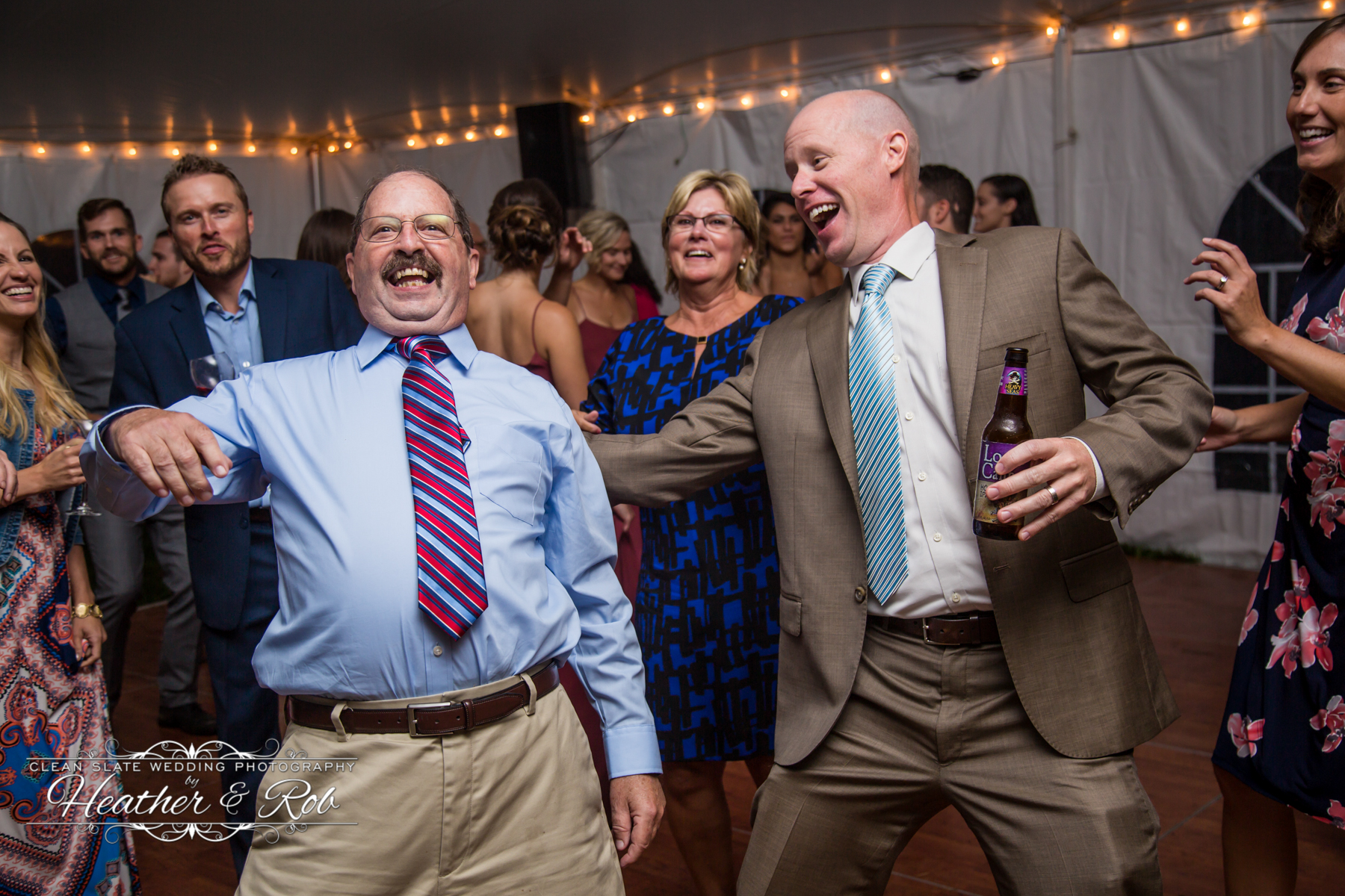 guys and wedding guests laughing and dancing