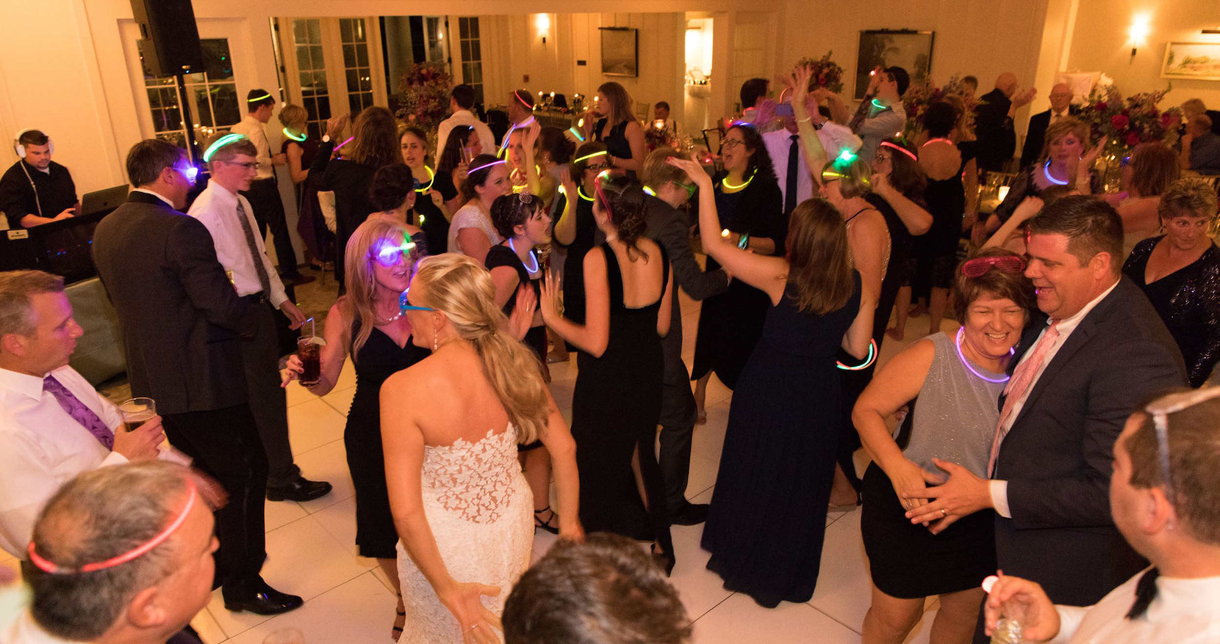 wedding guests dancing with glow sticks on