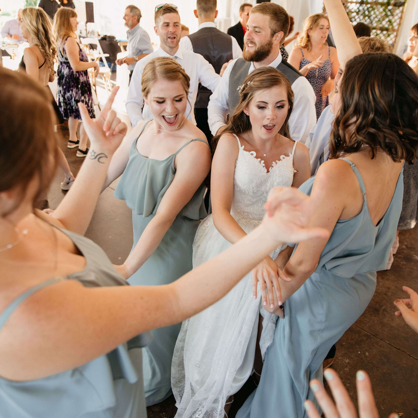 bride dances in the middle of bridesmaid group