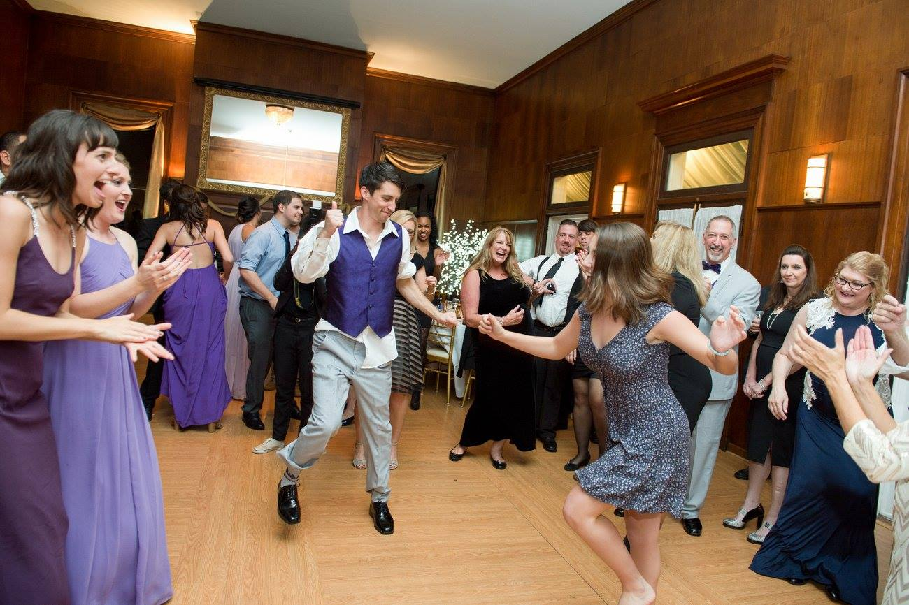 groomsman and woman dancing in the center at wedding