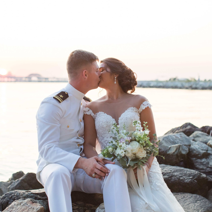 bride and groom kiss on rocks by water during sunset