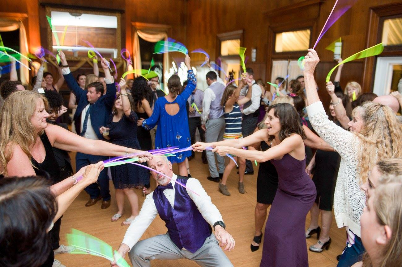 father of the bride doing limbo underneath glow sticks held by guests at weddings