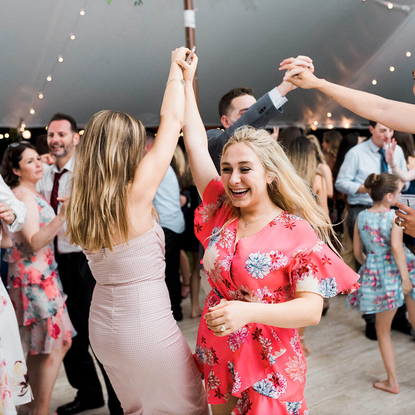 blonde woman in flower dress dances with friends