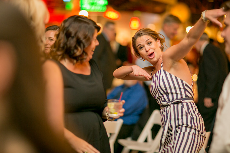 woman in striped dress dances at wedding