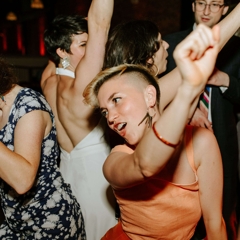 woman with short haircut in peach colored dress dancing