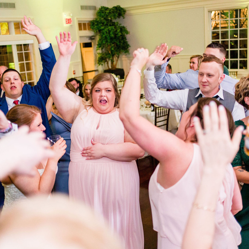 bridesmaids and guests dance with hands up