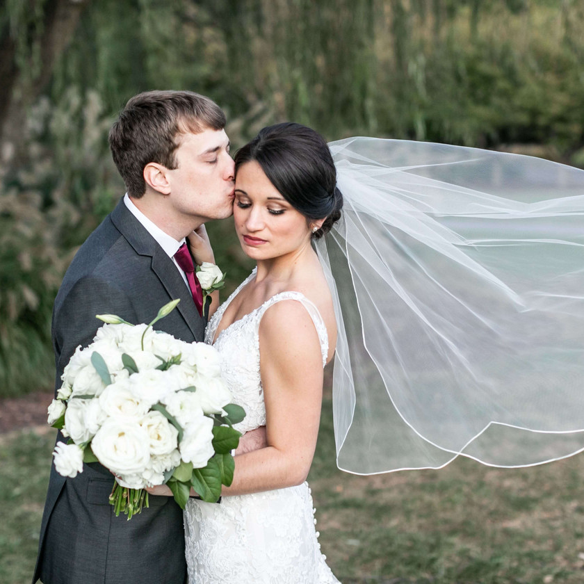 groom kisses bride's cheek outside