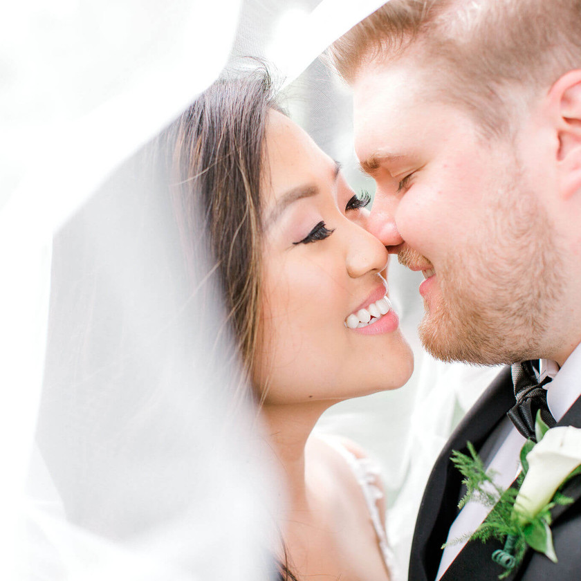 bride and groom about to kiss underneath veil