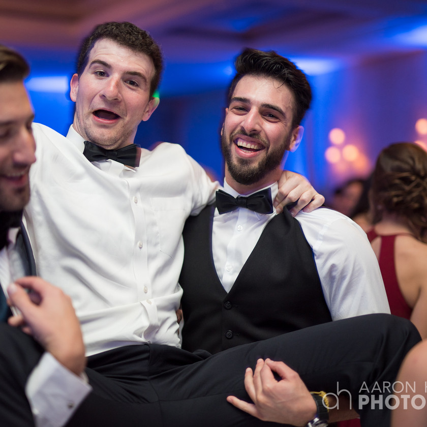 two guys hold up another guy between them