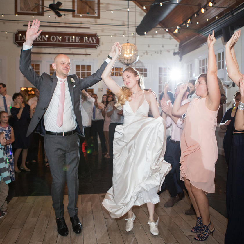 bride and groom jump up while dancing with friends