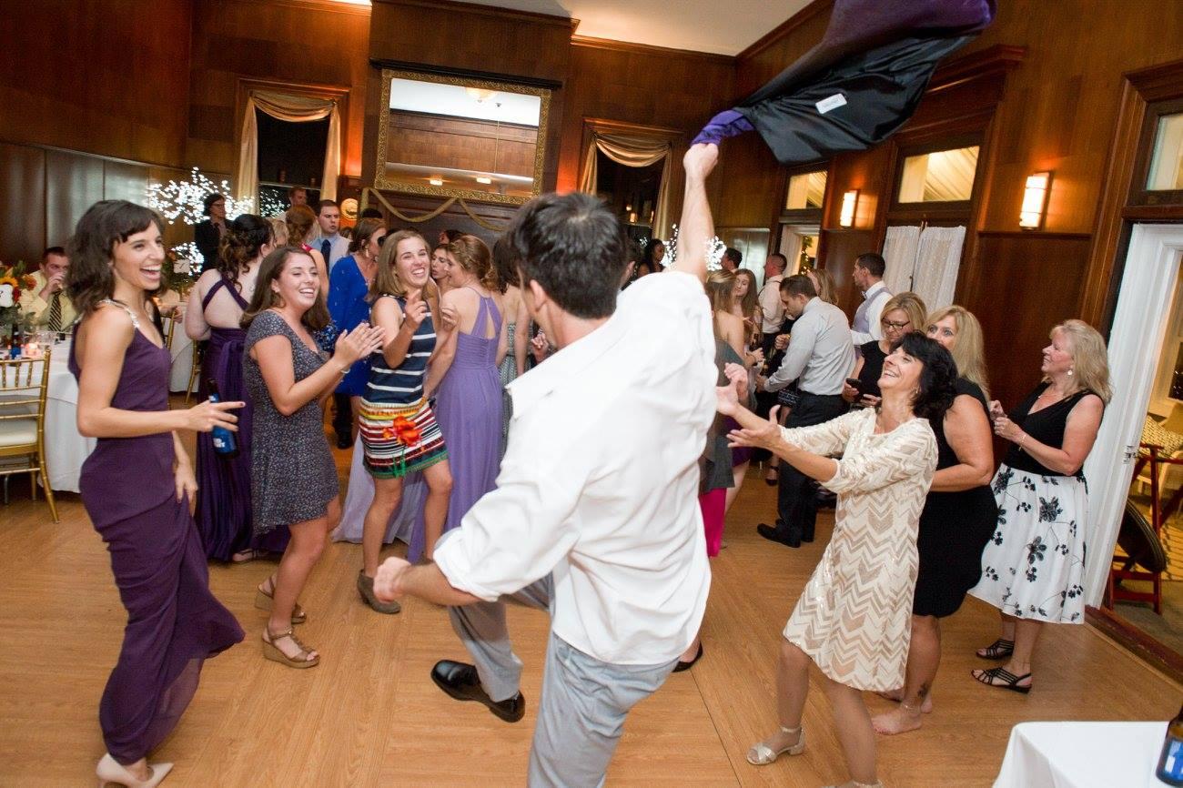groomsman waves around vest while girls watch at wedding
