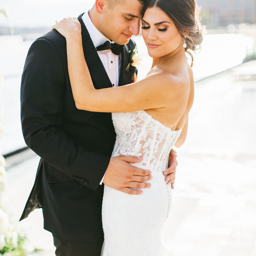 bride and groom pose outside