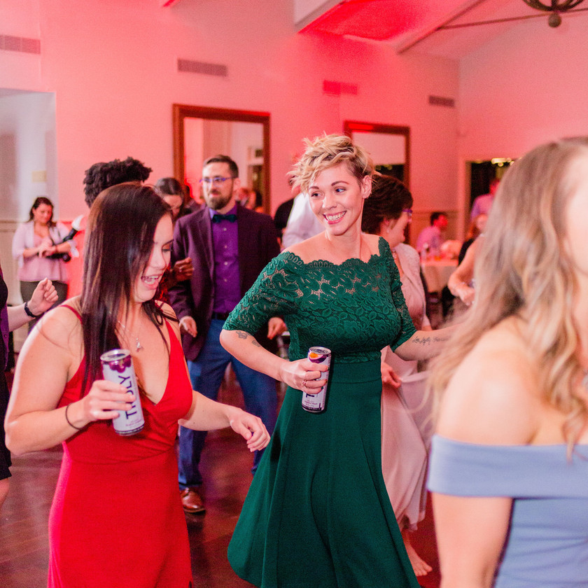 woman in green dress dancing and looking at woman in red dress at wedding