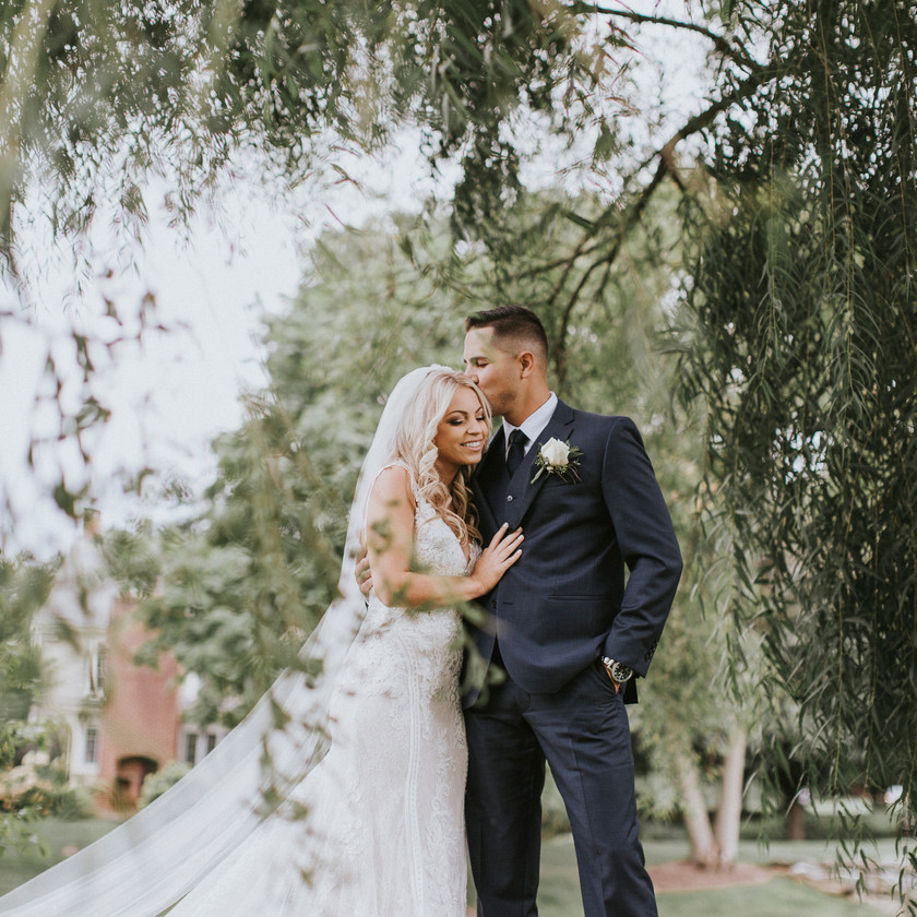 groom kissing bride on head while standing under a tree