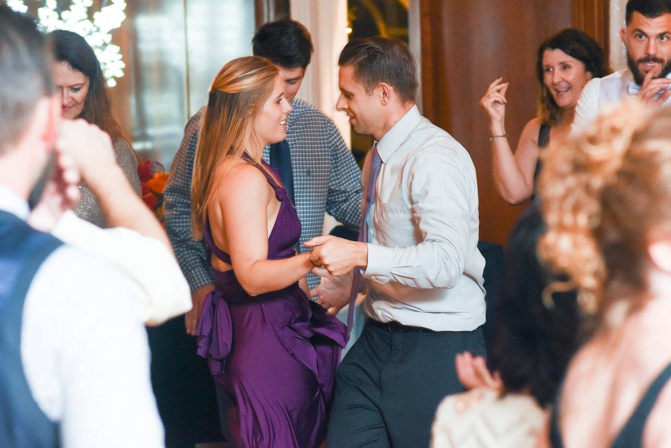 bridesmaid and man dance together