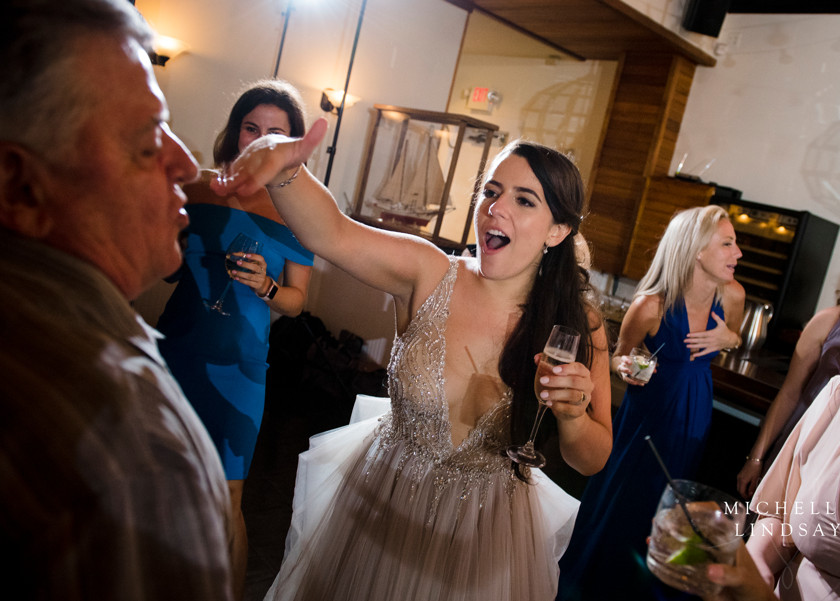bride holds champagne and dances at chesapeake bay beach club